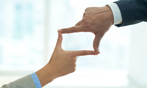 Businessman and businesswoman doing finger frame together